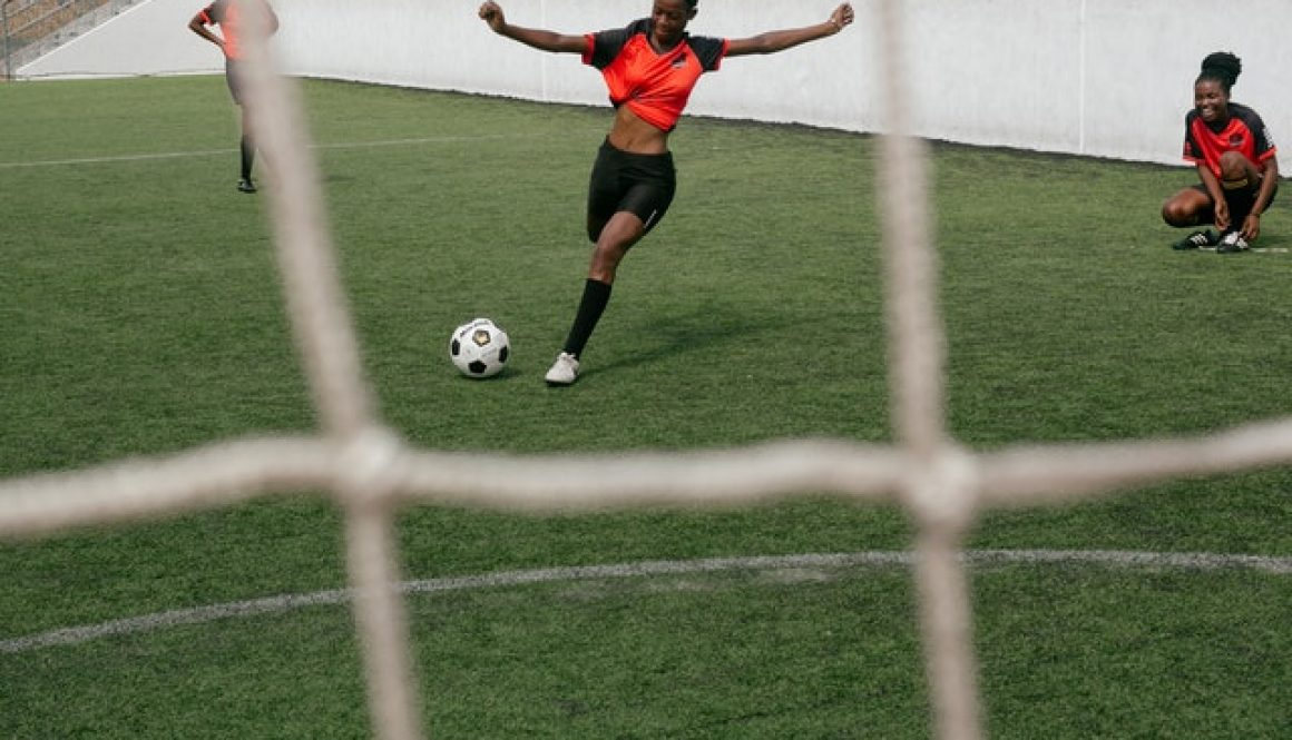 girl-in-red-shirt-and-black-shorts-kicking-a-soccer-ball-3886248